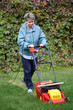 Middle Age Woman Mowing the Lawn