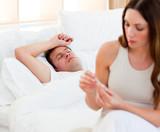 Concerned woman taking her sick husband's temperature