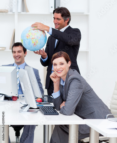 Happy manager holding a globe with his team working at computers