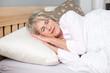 seniorin liegt im bett und schläft - 21010956