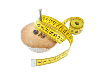 Diet concept, nailed down cake and measuring tape isolated