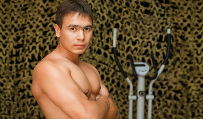 strong bodybuilder training muscles in gym, posing at camera