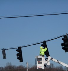 Guy working on traffic lights wearing a green safety jacket.