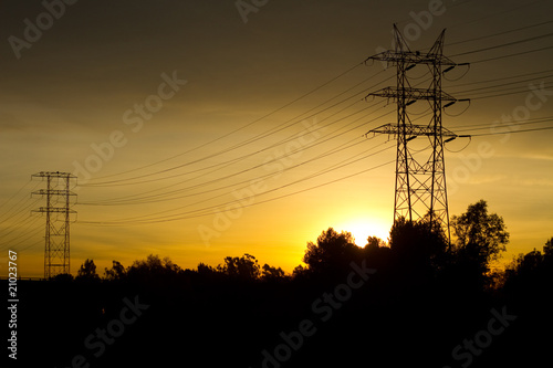 Electrical Tranmission Towers and Cables Against Golden Sky At S