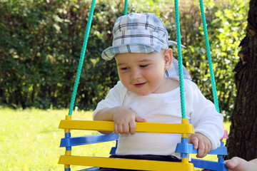 rocking child in gardens on swing