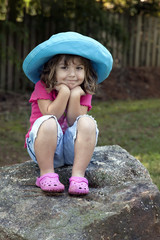 Little girl outdoors on large rock wearing shorts and hat