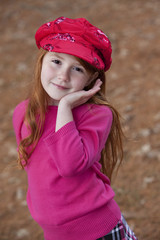 Beautiful little redheaded girl outdoors in red hat