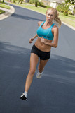 Beautiful Blond Woman Running and Listening to MP3 Player-