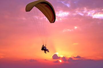 Flight of paraplane above Mediterranean sea on sunset