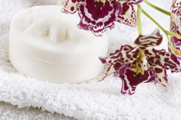 Spa items with white towels, natural soap and orchid