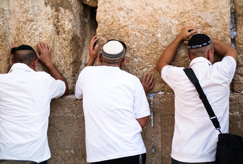 Three Jewish men at the Western Wall in Jerusalem