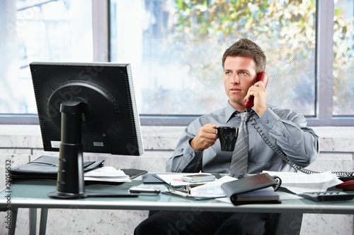 Businessman calling at office with mug