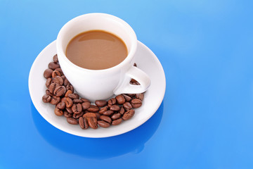 Small white   cup of coffee with coffee grain   on blue backgrou
