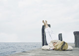 Woman lying at back and realaxing at a boardwalk