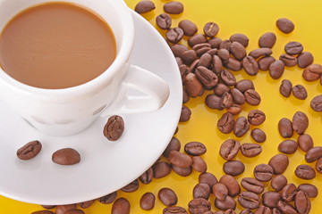 Small white  cup of coffee with coffee grain    on yellow backgr