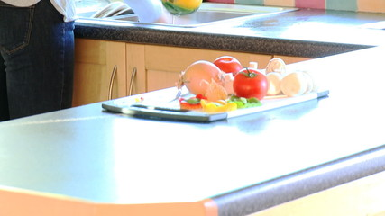 Young woman rinsing vegetables in the kitchen to make a salad