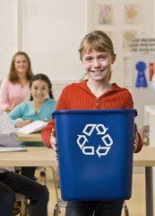 Girl holding recycling bin