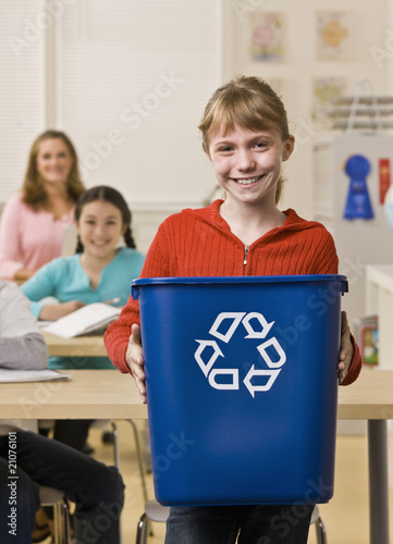 Girl holding recycling bin