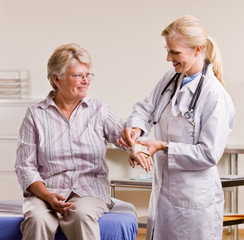 Doctor adjusting senior woman wrist splint