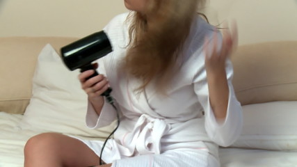 Blond woman using a blow-dryer in her bedroom