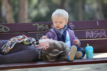 baby girl feeding her mother on bench in park