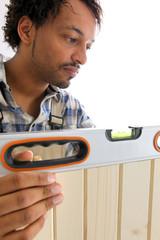 Menuisier mesurant planche de bois avec niveau à bulles