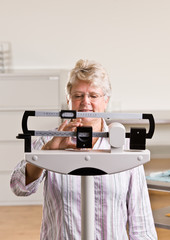 Senior woman weighing herself in doctor office