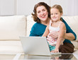 Grandmother and granddaughter using laptop