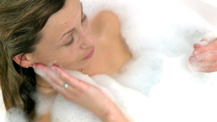 Charming woman having a bath at home