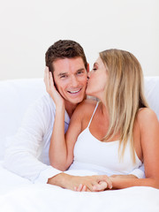 Intimate woman kissing her husband sitting on bed