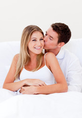 Affectionate man kissing his wife sitting on bed