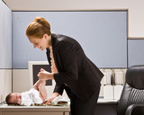Businesswoman changing baby diaper at desk