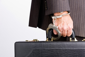 Businessman handcuffed to briefcase