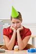 Businesswoman in party hat with birthday cupcake