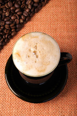 Background of the coffee beans and sackcloth with cup
