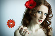 The beautiful young girl with a red flower and caramel