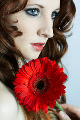 The beautiful young girl with a red flower