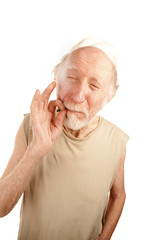 Senior man smoking cigarette or marijuana