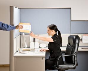 Businesswoman multi-tasking at desk in cubicle