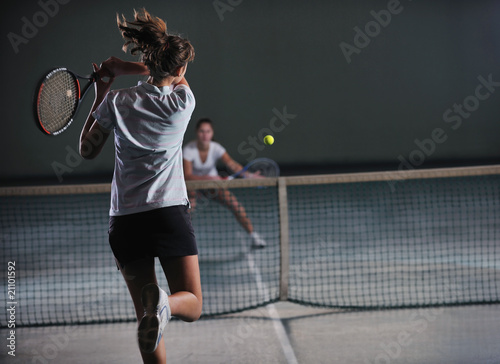 young girls playing tennis game indoor - 21101592