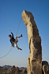 Female rock climber falling.