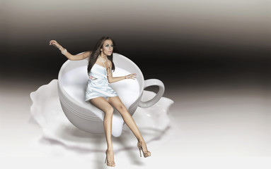 Dynamic photo of a young beauty in a cup of cappuccino