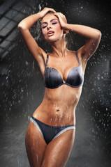Sexy brunette taking a shower in a dark room