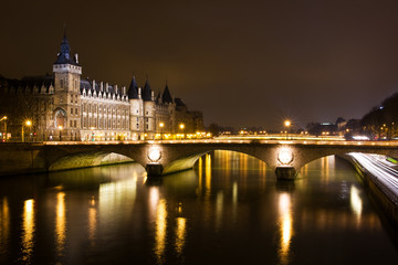 La Conciergerie and Pont au Change, over the Seine river at nigh