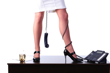 Legs of young businesswoman with phone cable on table