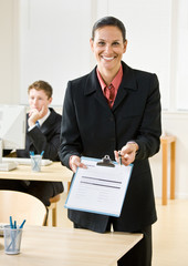 Businesswoman holding out clipboard and pen