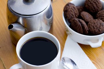 Cup of black coffee in a white mug and chocolate biscuits
