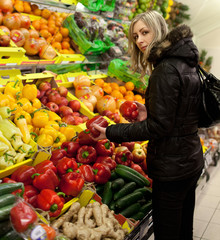 Beautiful young woman shopping for fruits and vegetables at a su