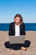 business woman sitting on the sand with laptop