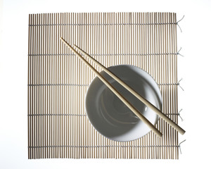 bamboo place mat with white cup and a pair of chopsticks